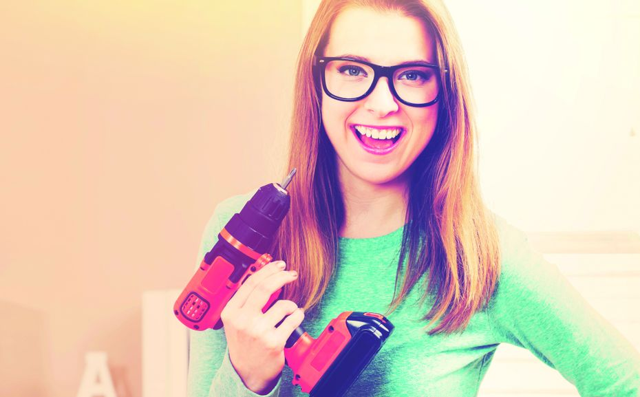 Young woman with cordless drill