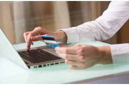 Man's hand entering data using laptop while holding a credit card in the other hand