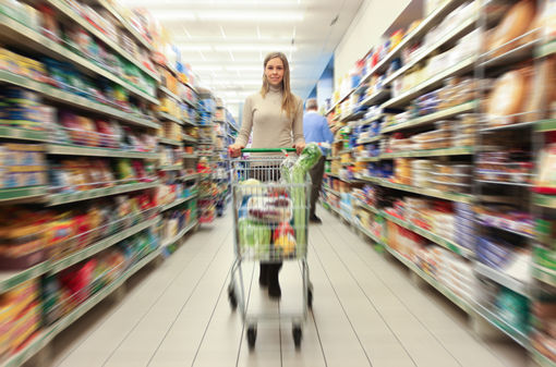 Woman driving a shopping cart in a grocery store. Radial blur effect