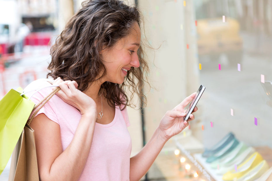 View of a Young attractive woman using mobile during shopping