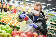 man in mask and protective gloves buying fruit food it supermarket shop during quarantine for covid-19 virus outbreak
