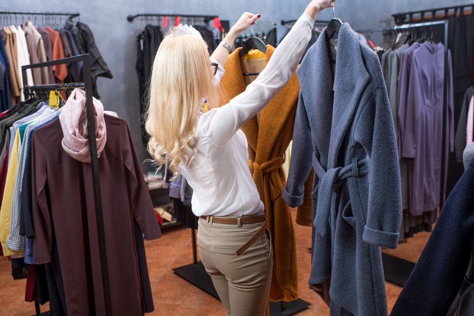 Beautiful blonde woman choosing coat in the clothing store
